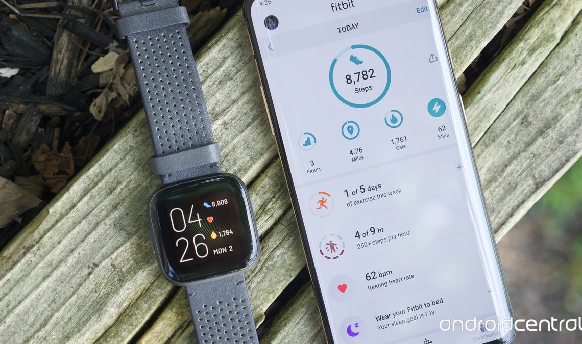 Fitbit Versa 2 next to a OnePlus 7 Pro running the Fitbit mobile app