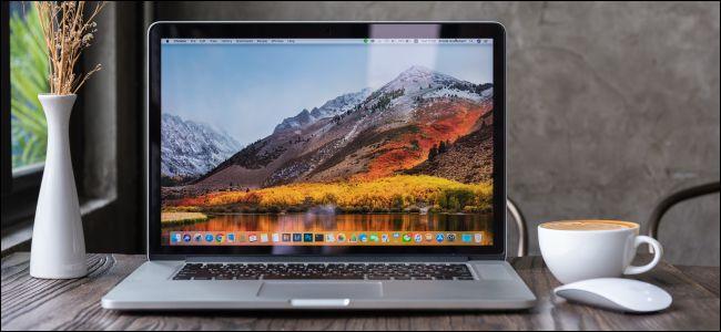 Ноутбук MacBook, открытый на деревянном столе.