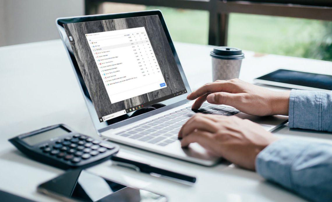 Человек, использующий диспетчер задач Chrome на ноутбуке в офисе