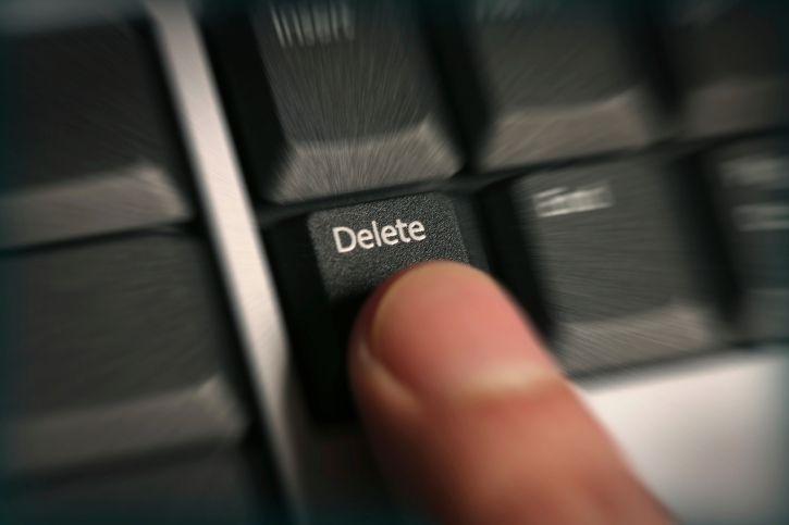 Фотография пальца, нажимающего кнопку удаления на клавиатуре