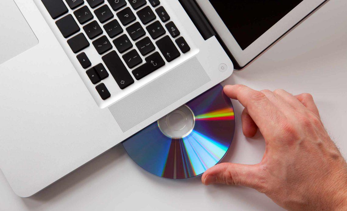 Рука вставляет диск в ноутбук