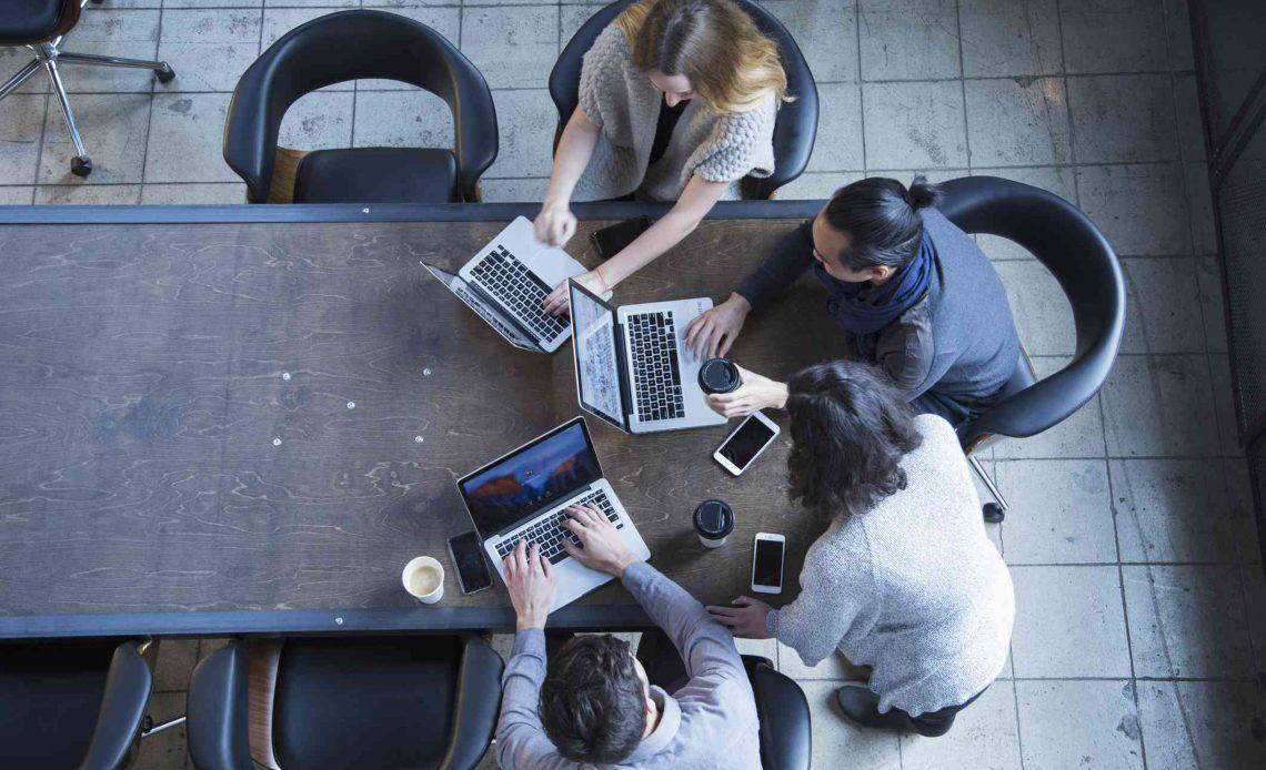 Группа людей, работающих за столом на ноутбуках