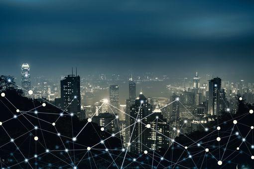 Городской пейзаж освещается ночью, на нем наложены линии для представления трафика данных