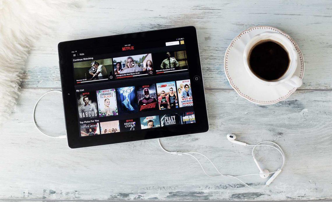 Netflix на iPad рядом с чашкой и блюдцем с кофе на деревянном полу