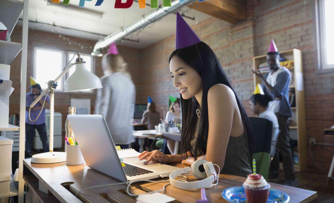 Коммерсантка нося шляпу вечеринки по случаю дня рождения на компьтер-книжке