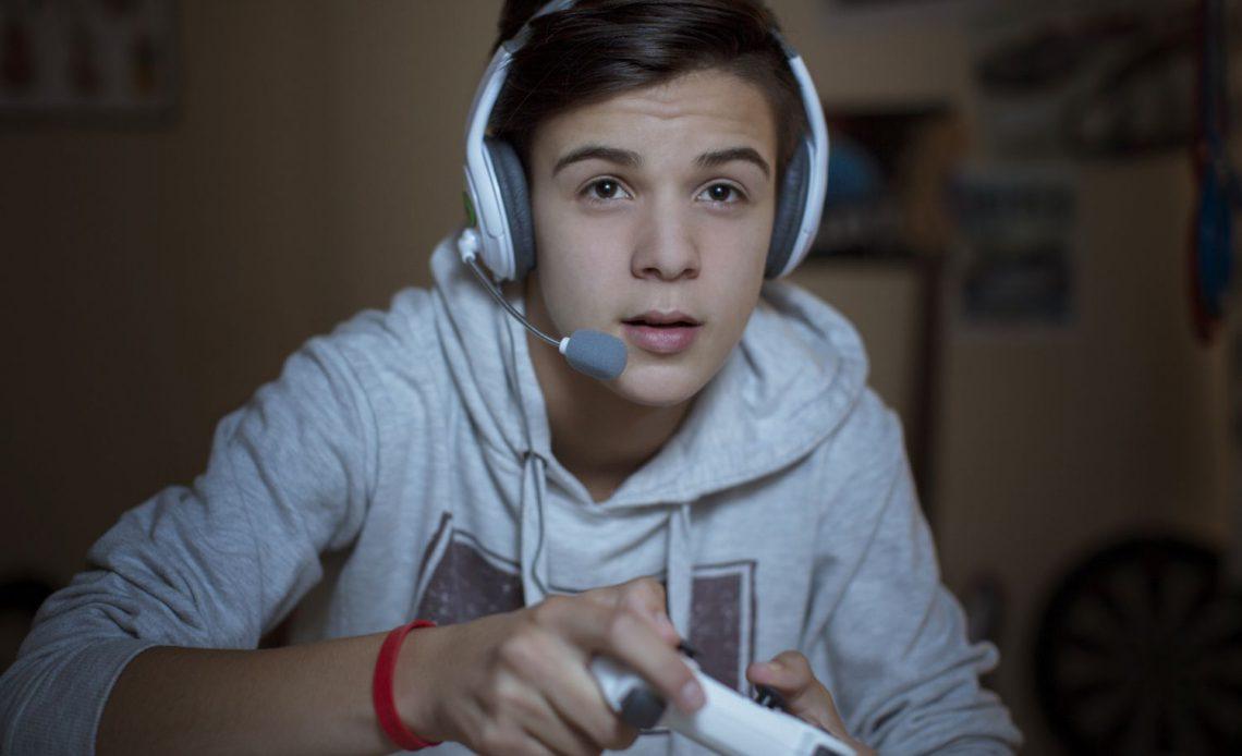 Подросток с игровой гарнитурой на видеоигре