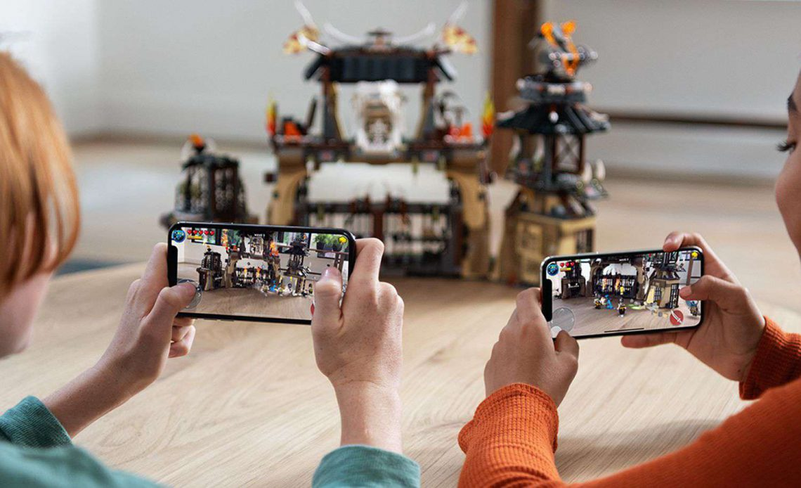Дети играют с дополненной реальностью на iPhone с замком Лего на заднем плане
