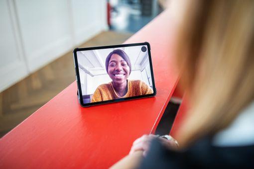 Женщина в приложении для видеоконференций, отображаемом через планшет